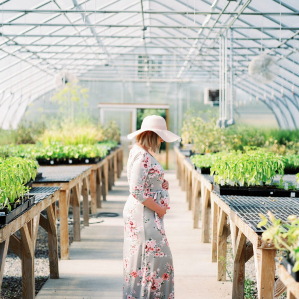 pregnant woman wearing hat in greenhouse amy rau photography