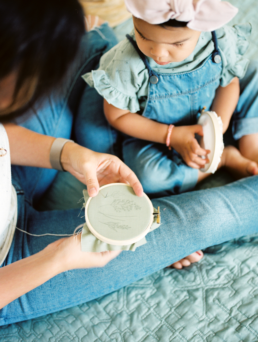 mother working on embroidery hoop with child