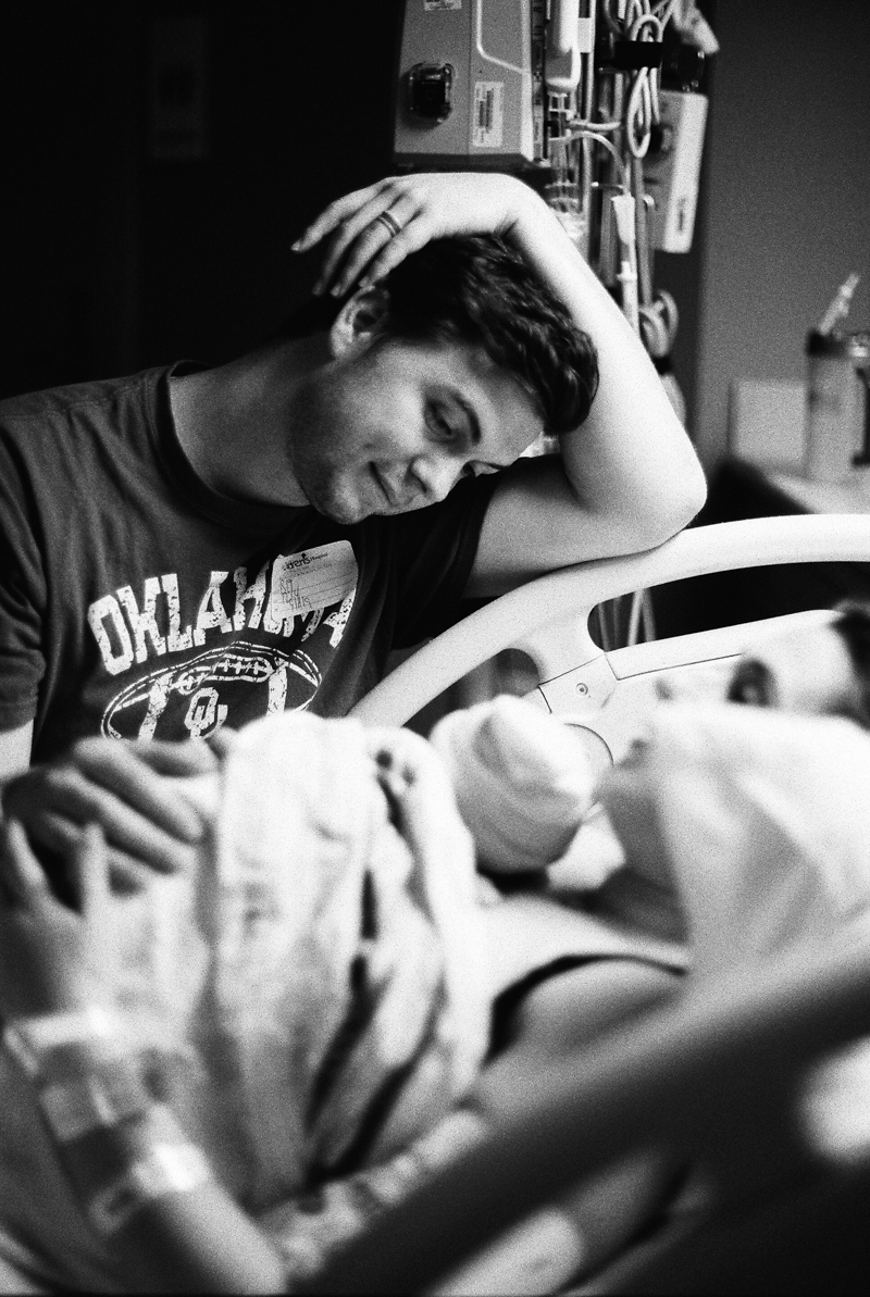 father looking down at newborn baby