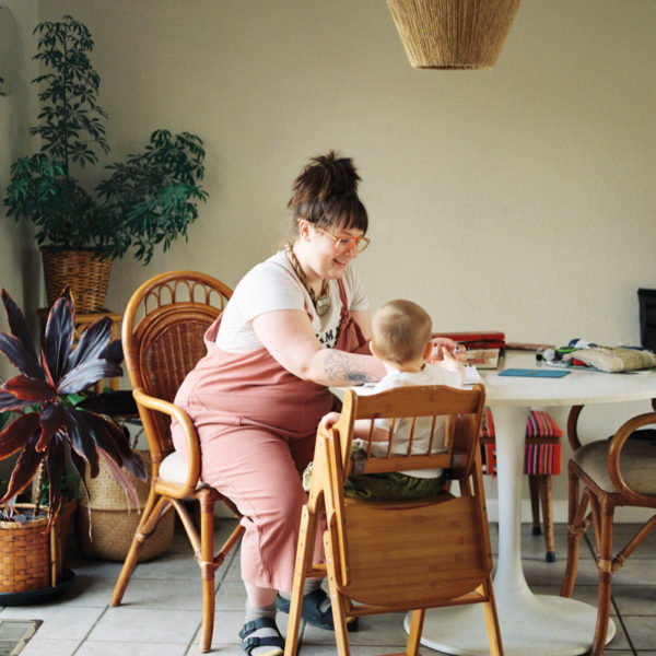 mother sitting at table with toddler in high chair
