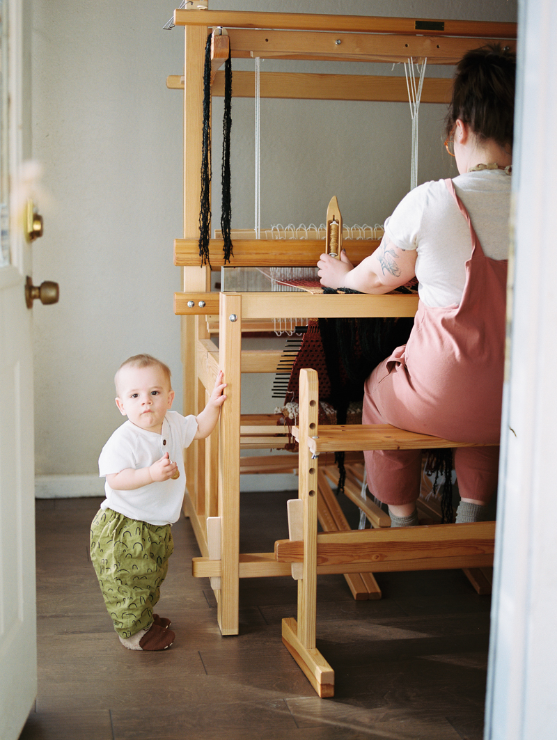 mother working on loom with child standing next to her