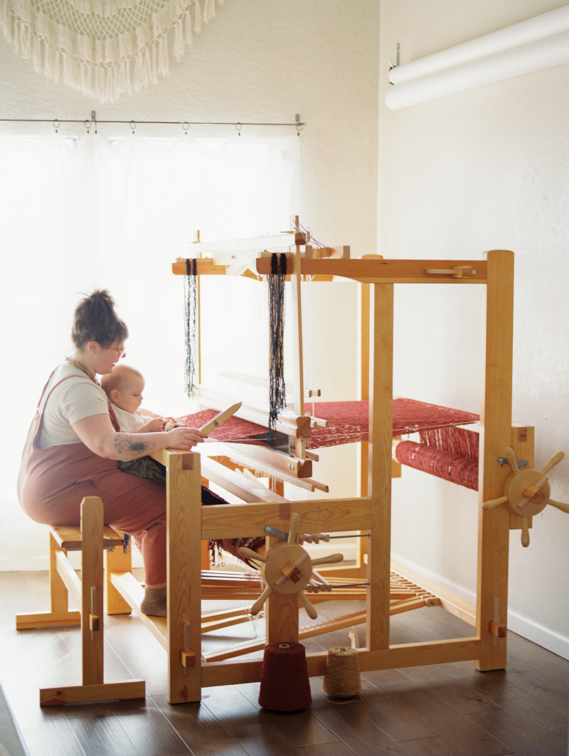 mother working on loom with son