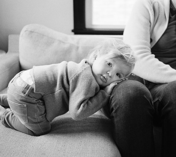little boy laying on father's knee