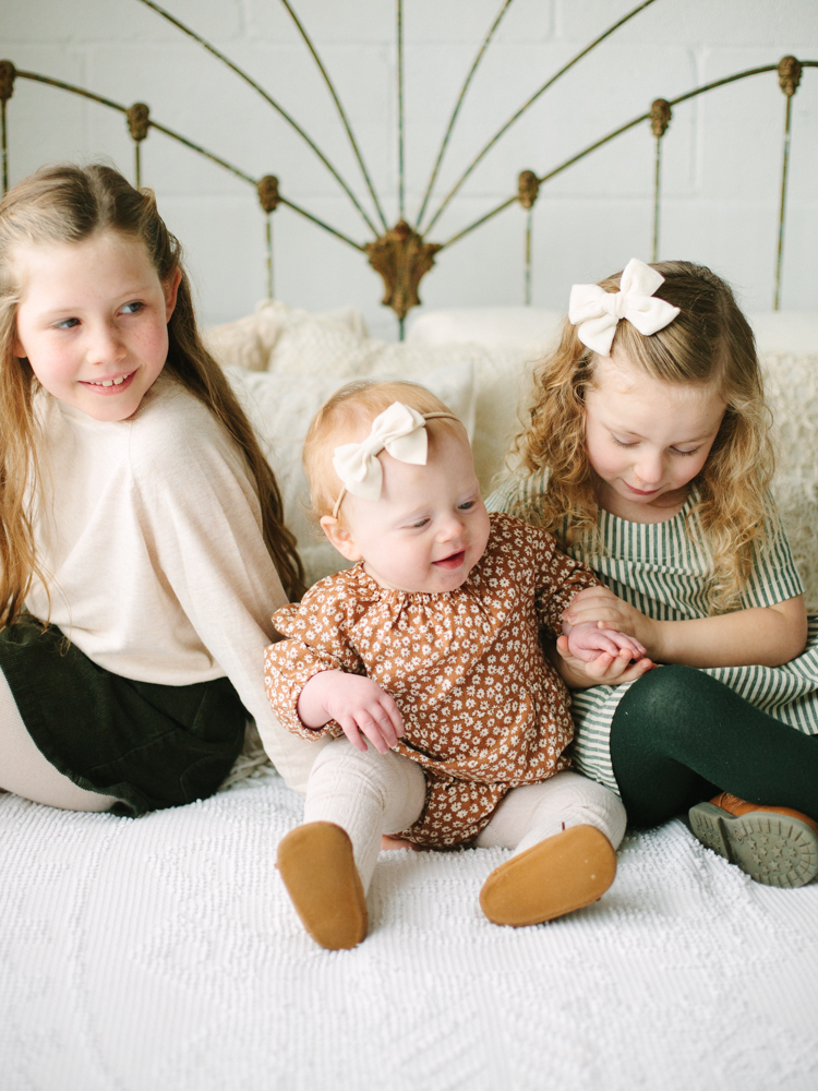 three little sisters sitting on a bed