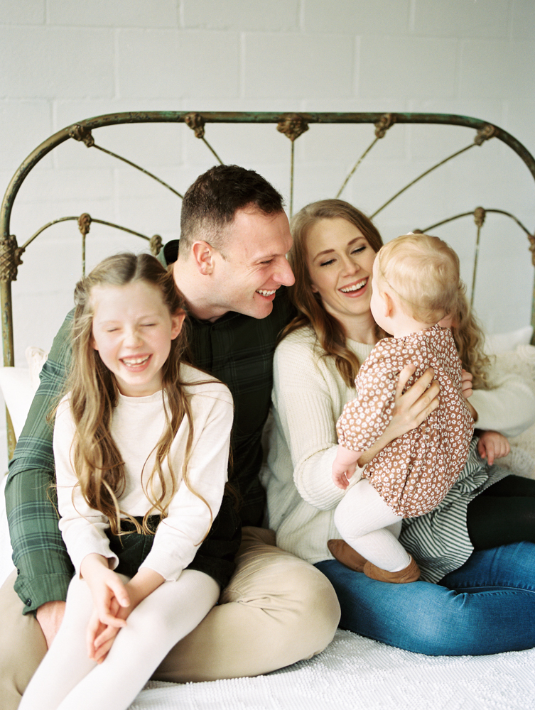 family sitting on bed laughing